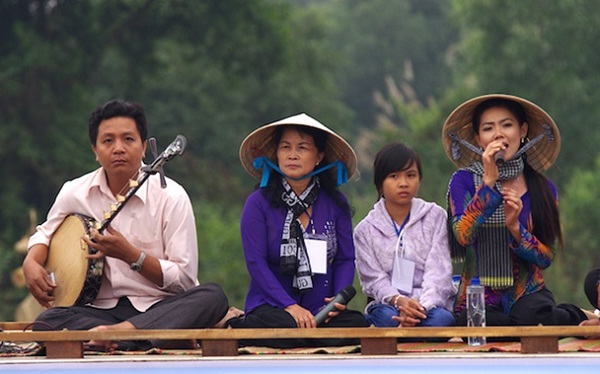 "Travellers listening to ""Đờn ca tài tử"" while enjoying the beauty of Mekong River on boat"