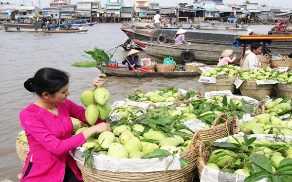 Small wooden boats on Mekong River are full of tropical fruits