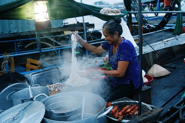A woman sells nem nuong and Hu Tieu (rice noodle soup)