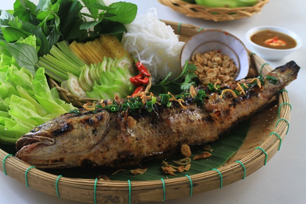 Grilled fish eaten with fresh vegetables which you can enjoy when exploring Mekong delta by boat