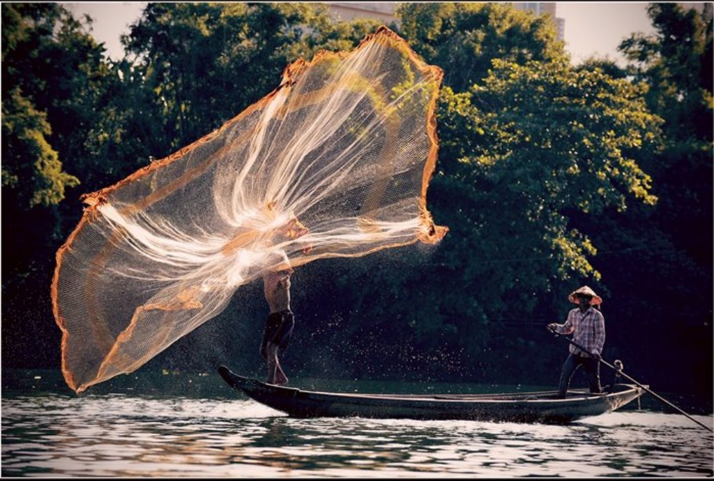 A fisherman is trying to hit the net as far as possible to catch much more fish