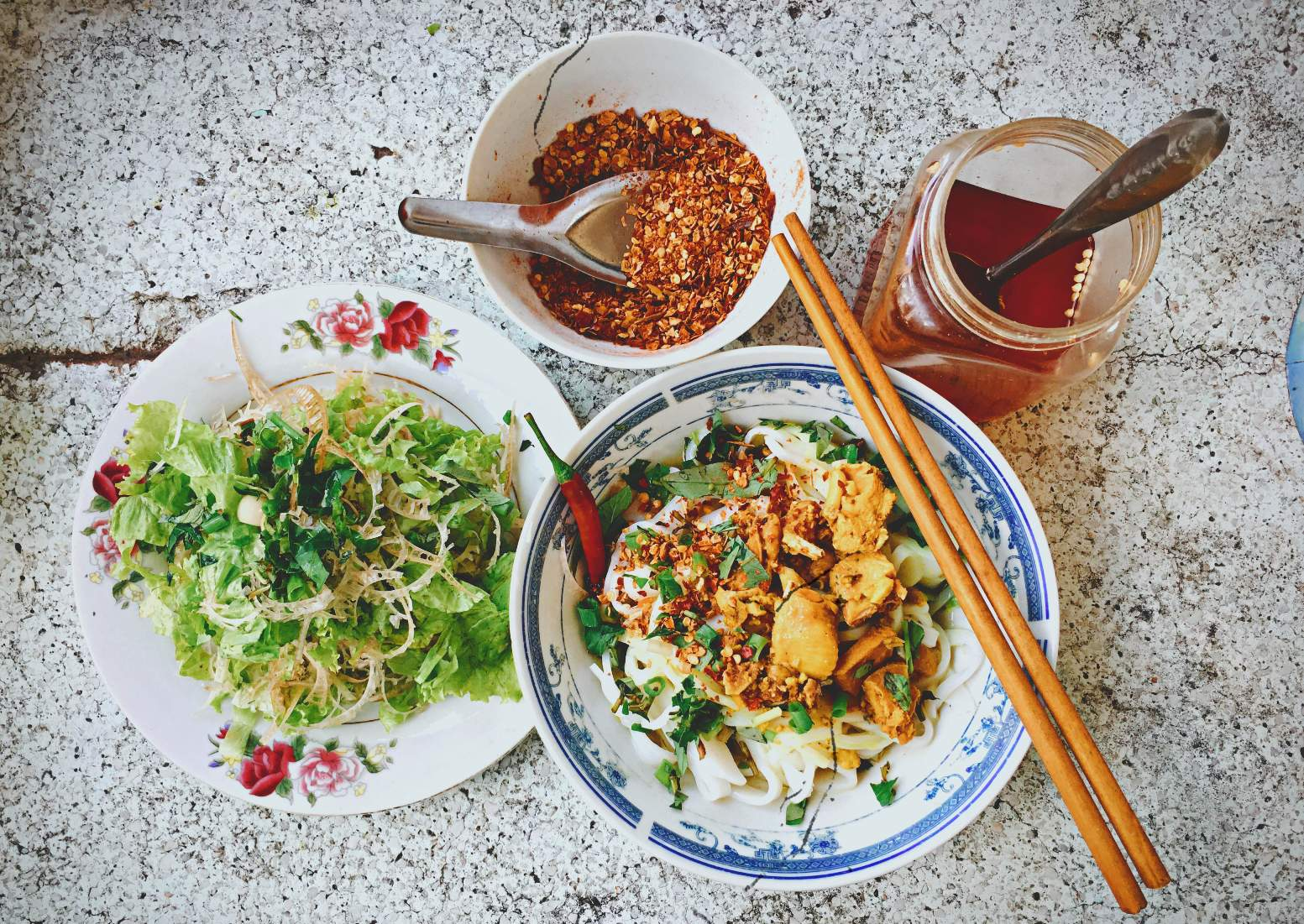 Quang noodle is served with fresh vegetables, chili and vinegar
