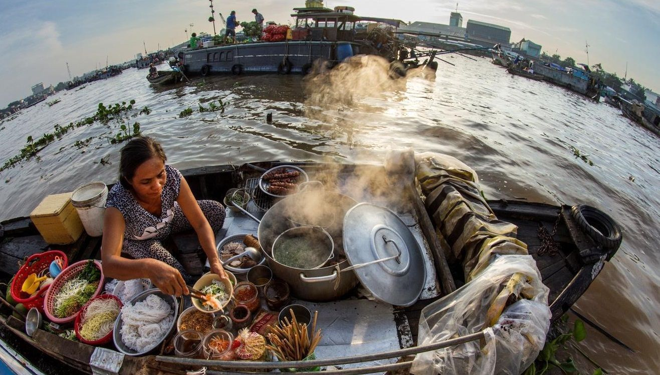 An old lady is selling Vietnamese traditional noodles on her own boat